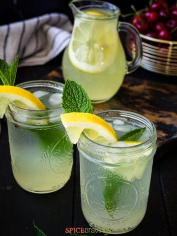 Fresh lemonade poured in mason jars with lemon slice and mint