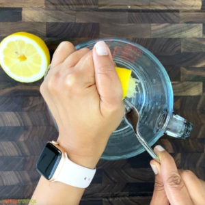 Squeezing lemon half with fork into glass measuring cup