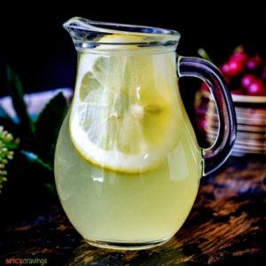 Lemonade in glass pitcher with large lemon slice