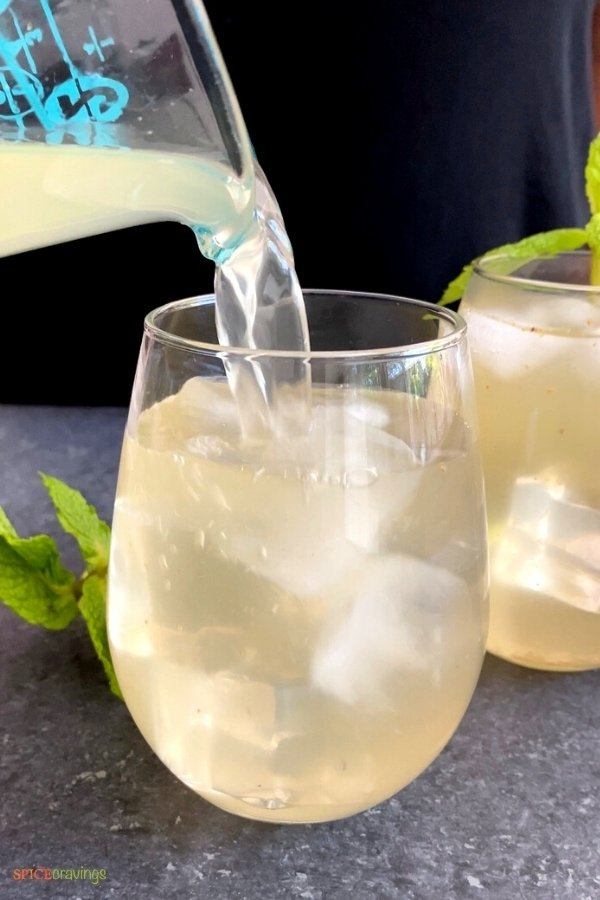Pouring Indian lemonade over ice