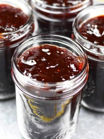 Four jars of plum jam on silver plate