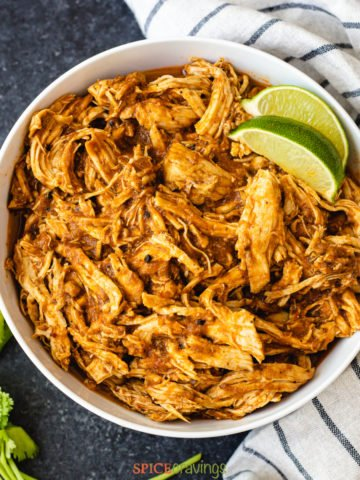 shredded chicken with lime wedges in a white bowl