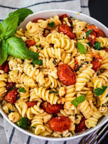 bowl of baked feta pasta garnished with basil