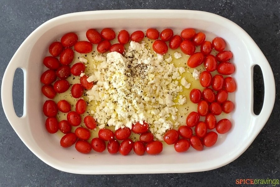 tomatoes and feta drizzled with olive oil in baking dish