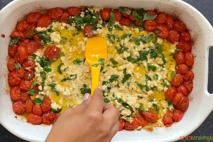 baked feta and tomato being mixed together with basil and garlic