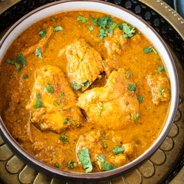 chicken curry in bowl on metal plate