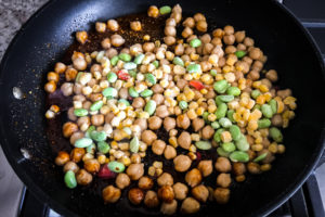 Frozen soycutash mix along with chickpeas in pan