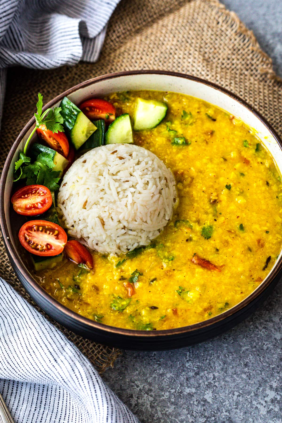 bowl of moong dal topped with a scoop of cumin rice, and cucumber-tomato salad