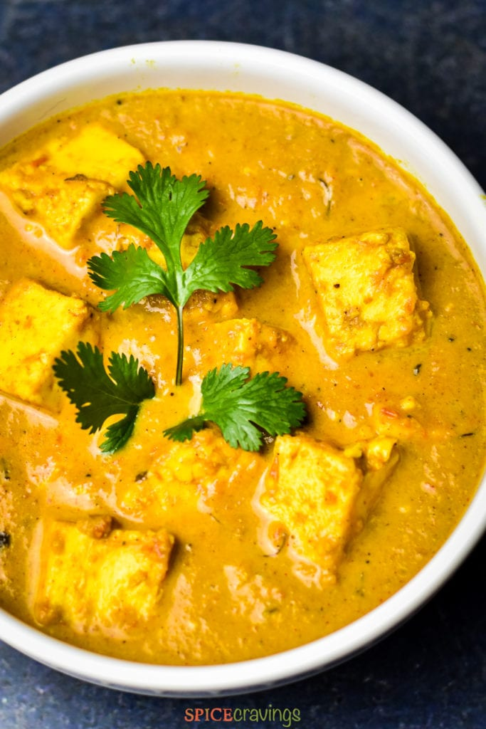bowl of paneer butter masala garnished with fresh cilantro
