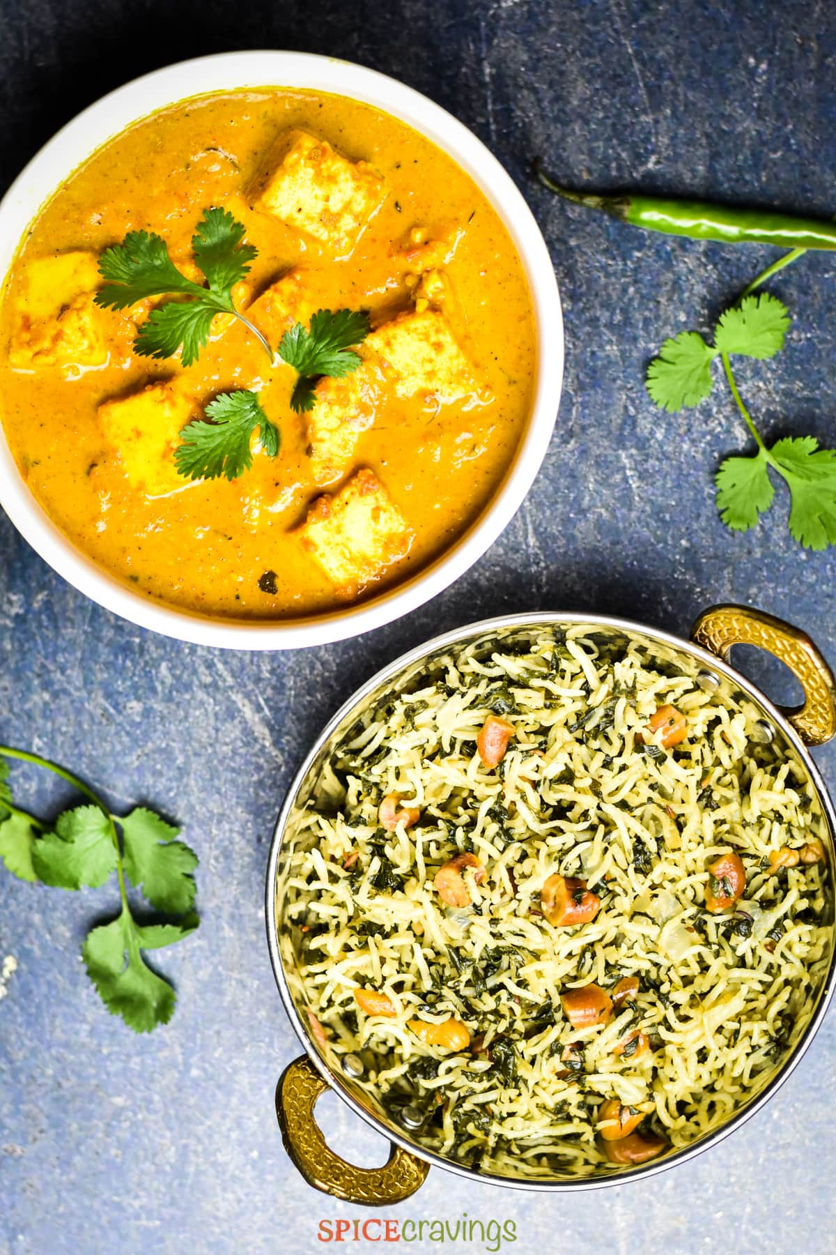 bowl of paneer makhani garnished with cilantro next to a bowl of spinach rice