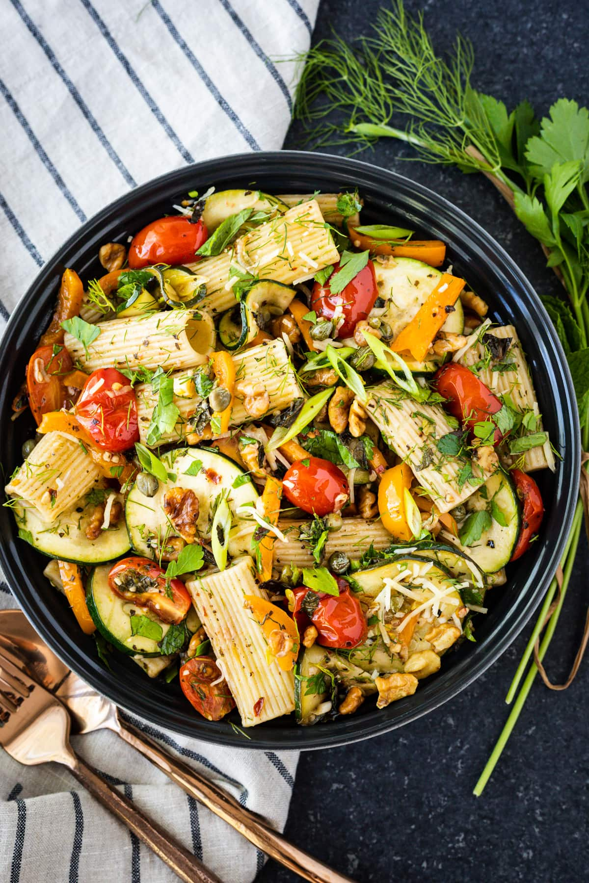 bowl of pasta salad garnished with fresh herbs