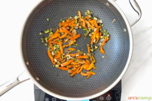 green onions and bell pepper being sautéed with seasonings in skillet