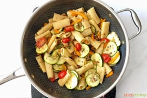 cooked pasta added to veggie mixture in skillet