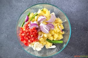 cut cauliflower, potatoes, onion, tomato in mixing bowl
