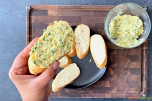 bread being covered with homemade garlic butter