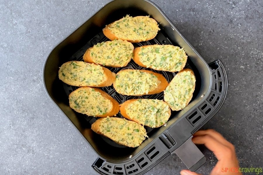 garlic bread covered in garlic butter in air fryer basket