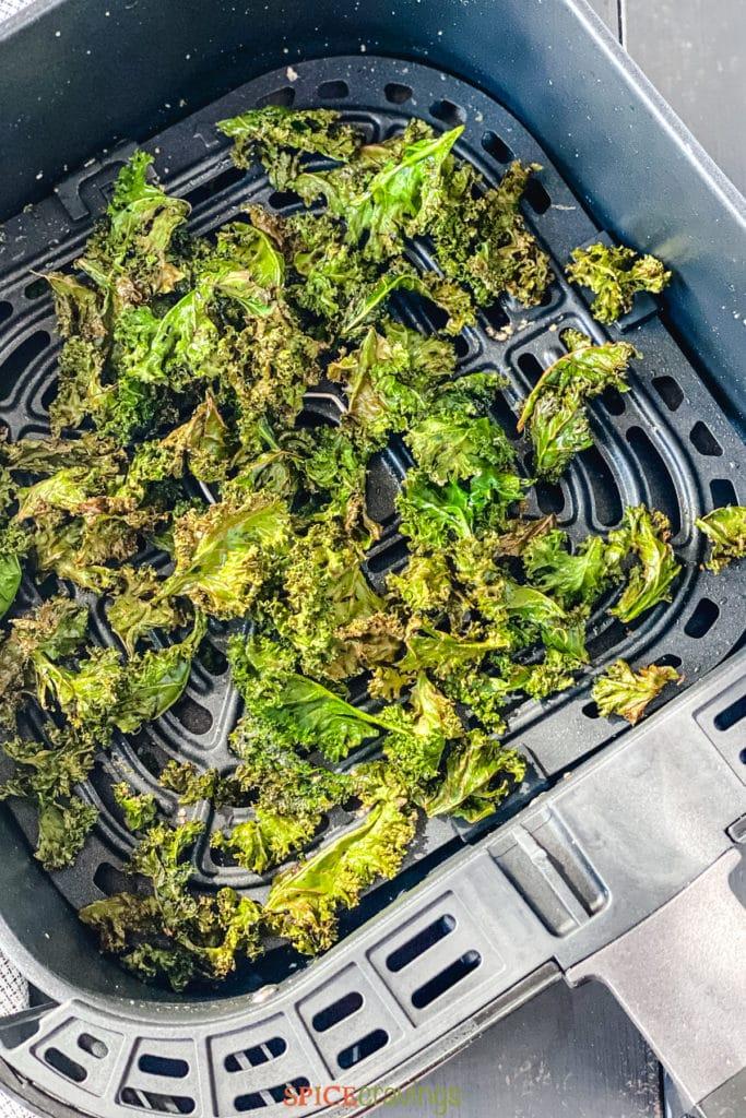 Crisped kale leaves in air fryer basket