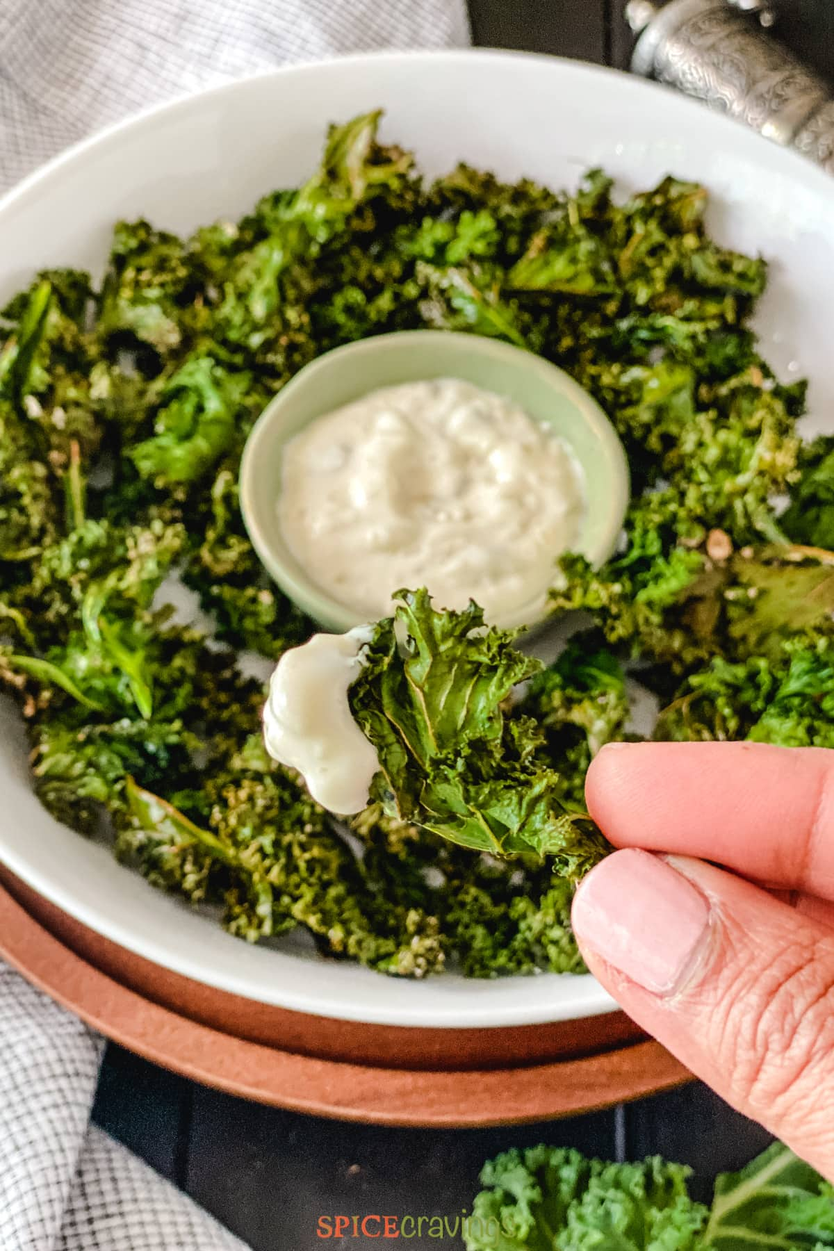 Hand holding Kale chip dipped in lemon caper sauce