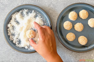 Dipping coconut fudge ball in desiccated coconut