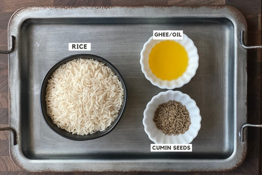 Bowl of rice, ghee and cumin seeds on a metal tray