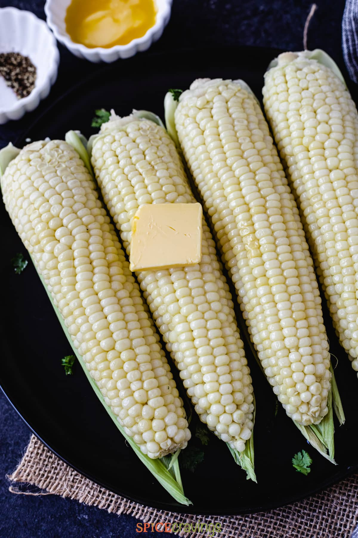 four cobs of corn on a plate topped with butter