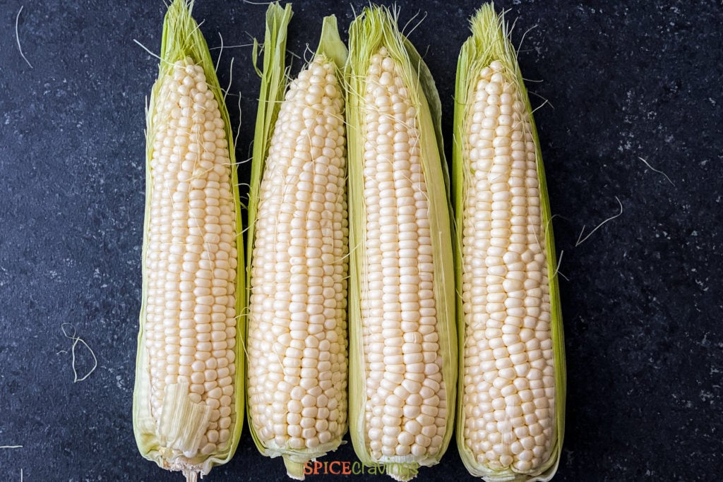 four cobs of corn lined up on counter