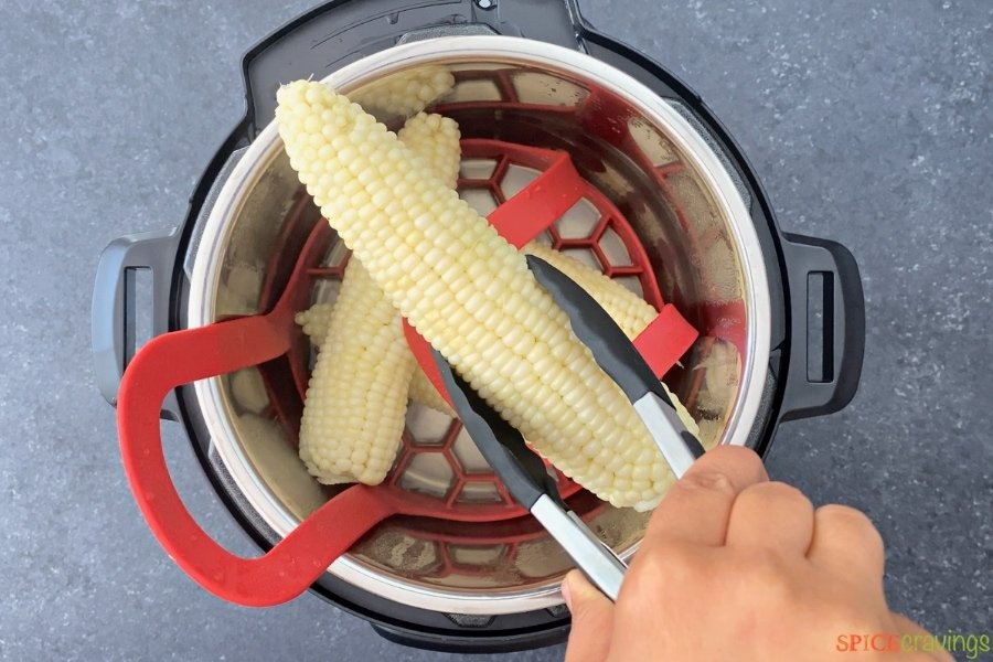 cooked corn on the cob being removed from the instant pot