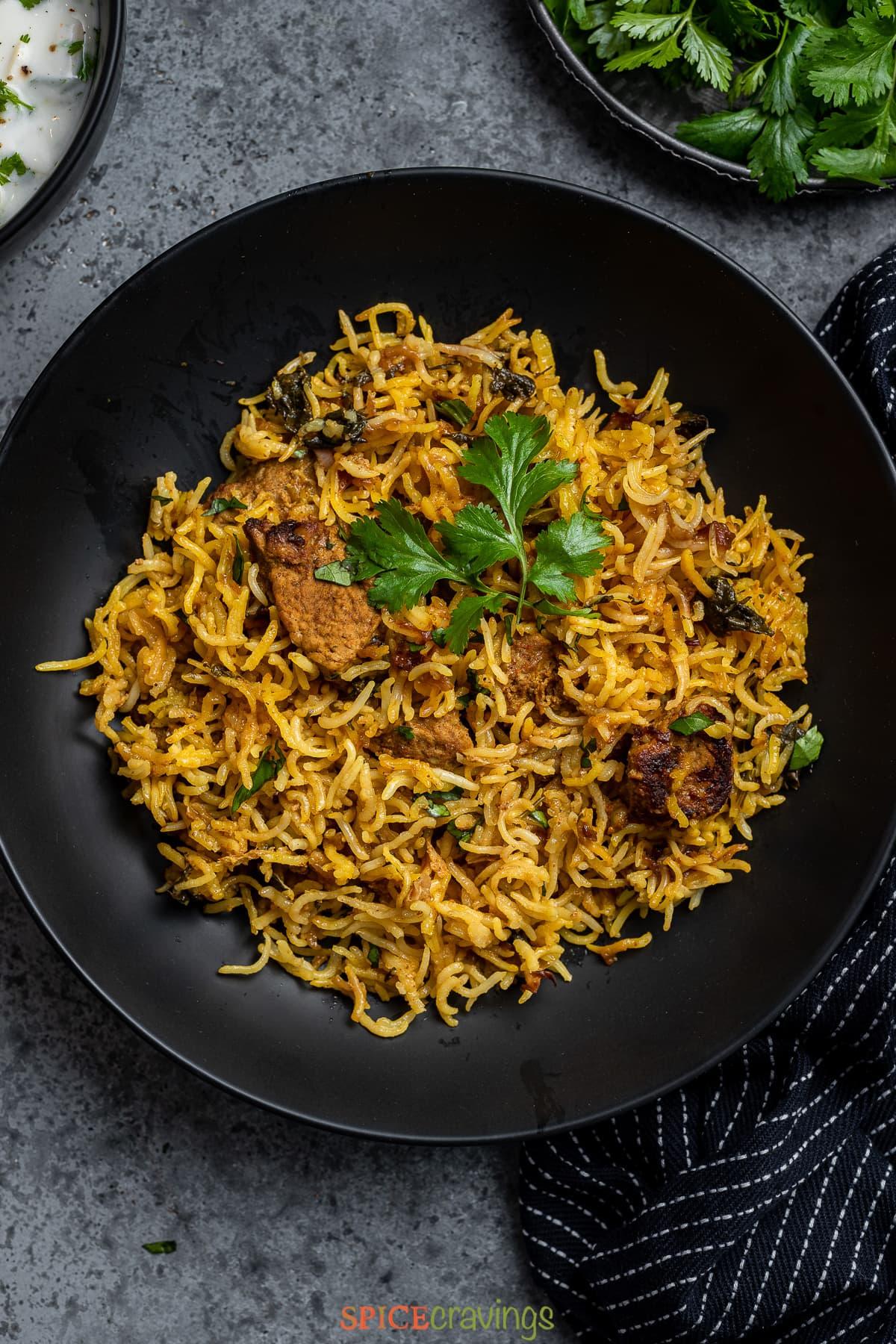 Lamb and rice in black bowl