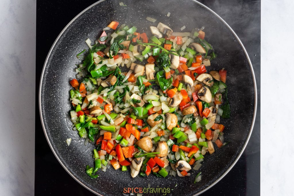 Sauteing chopped vegetables in skillet