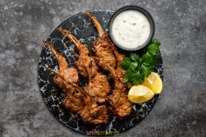 lamb chops on plate with tzatziki, parsley and lemon wedges